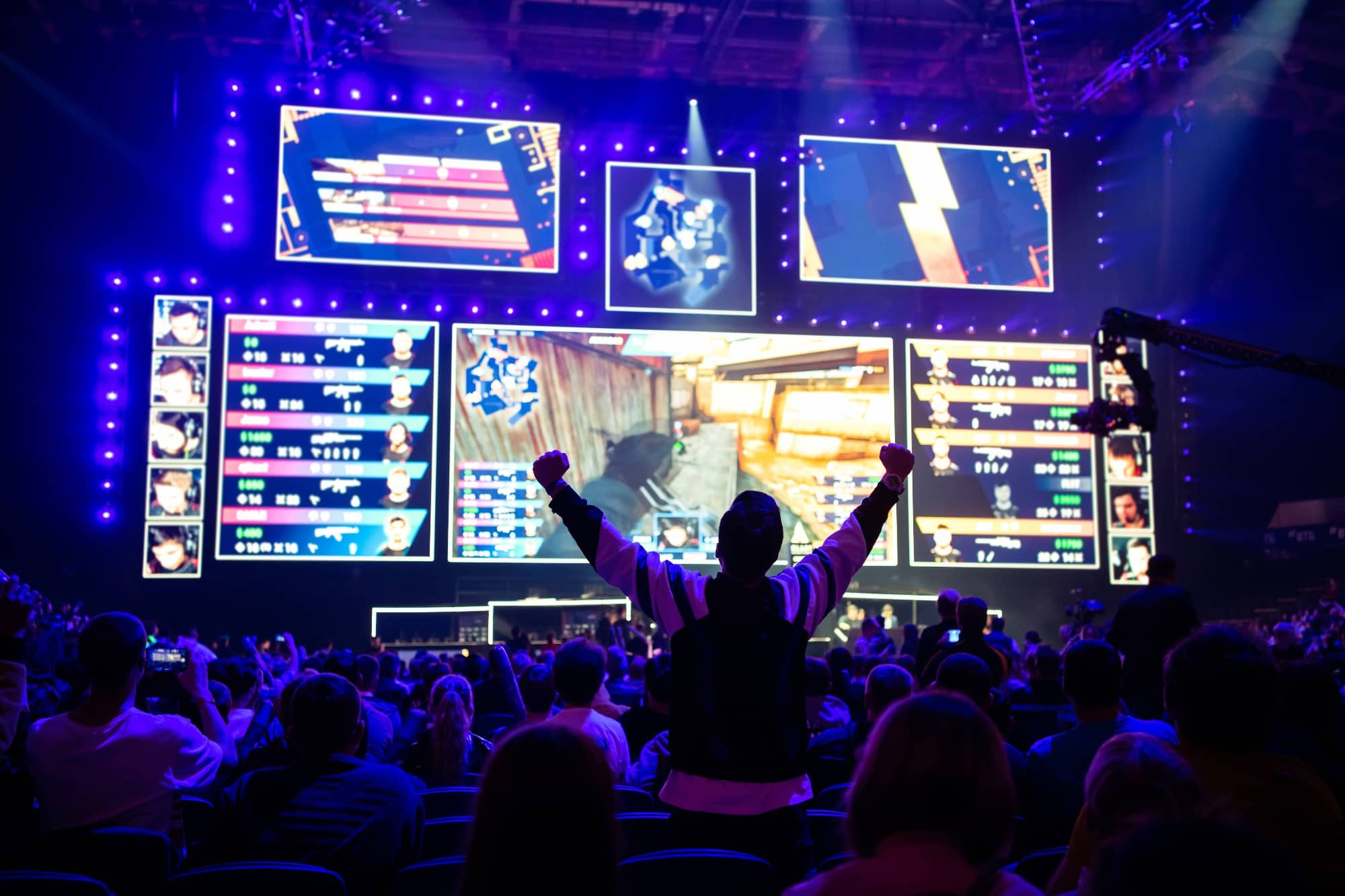 Big esports event. Video games fan on a tribune at tournament's arena with hands raised. Cheering for his favorite team
