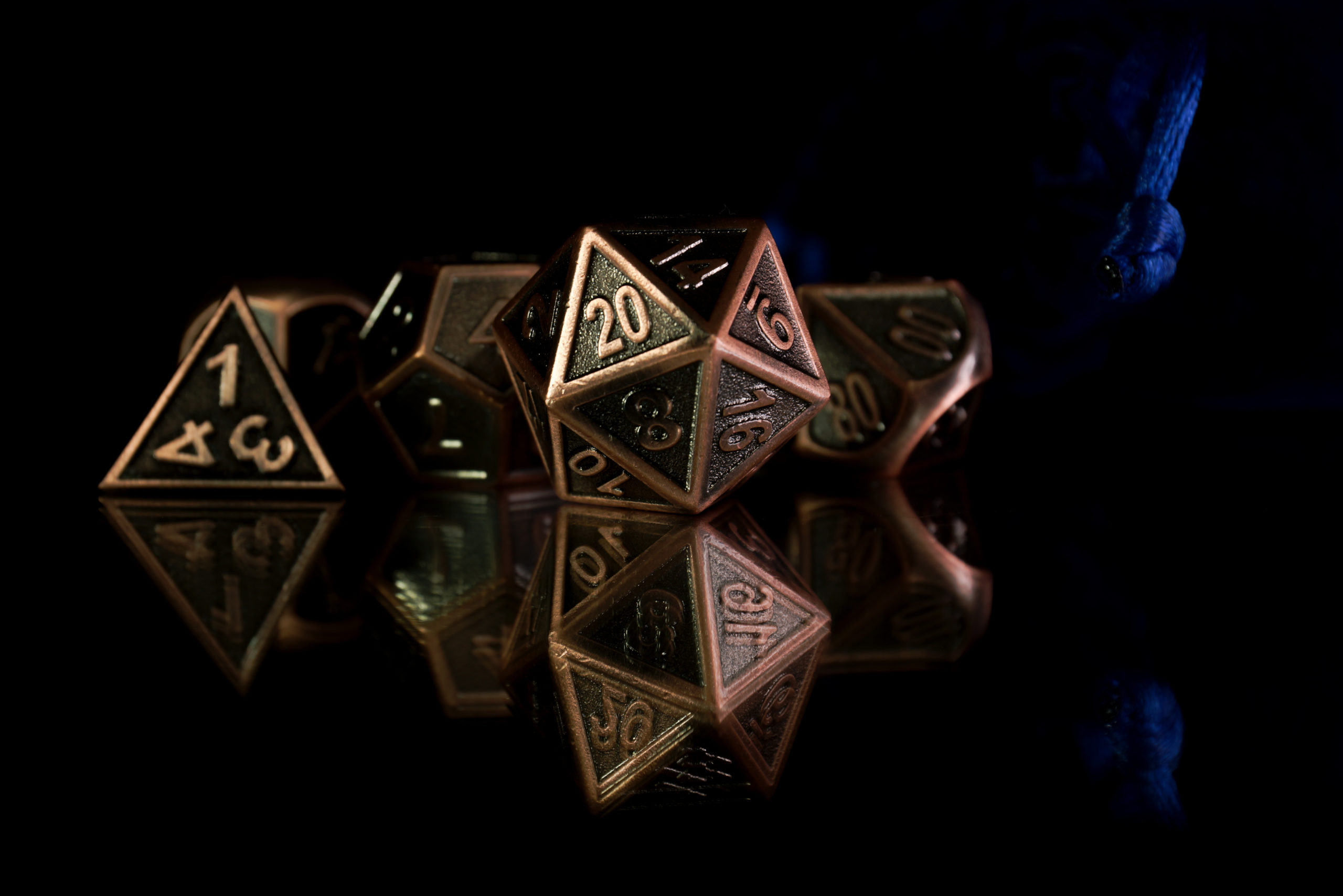 A set of polyhedral dice  with a blue drawstring bag on a mirrored surface. These dice are used for role playing games such as Dungeons & Dragons.